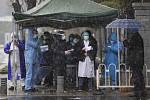 Vládní pracovníci čekají na pacienty, kteří dorazí 15. února 2020 do nemocnice ve Wu-chanu, která je určena k léčbě pacientů nakažených koronavirem COVID-19