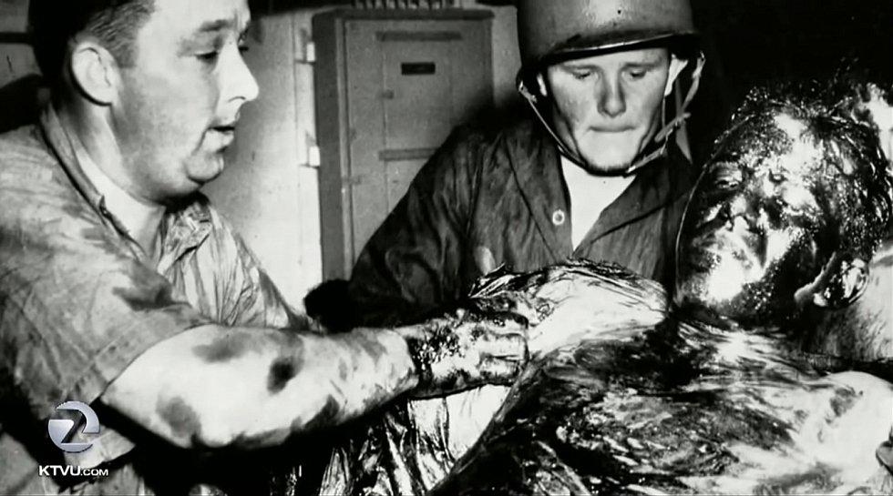 Zdravotníci zachraňují přeživšího námořníka z Indianapolisu pokrytého vyteklou naftou