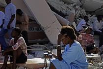 Žena na Haiti se modlí vedle zbořeného kostela v hlavním městě Haiti Port-au-Prince. I čtyři týdny po ničivém zemětřesení vyprostili záchranáři z trosek živého muže.