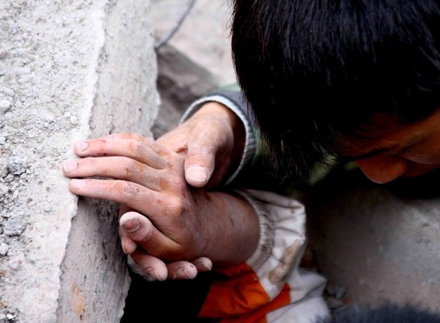 Záchranář se pokouší vyprostit uvízlého školáka ze zřícené školní budovy na předměstí Mien-cu.
