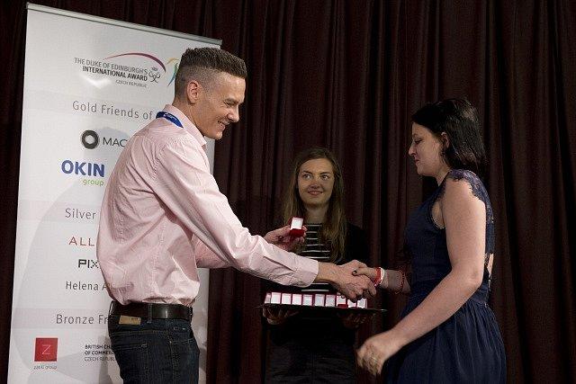 Zástupce britské velvyslankyně Angus Stewart předává ocenění jedné z dívek na předávání cen vévody z Edinburghu 6. června v sídle ministerstva kultury v Praze.