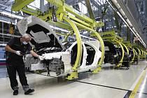 Zaměstnanec automobilky Mercedes-Benz pracuje s ochrannou rouškou na montážní lince