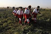 Záchranáři odnášejí tělo oběti nehody ukrajinského letounu, který se zřítil krátce po startu z teheránského letiště.