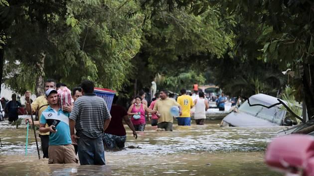Lidé se ve městě Planeta brodí po ulicích zaplavených po řádění hurikánu Eta.
