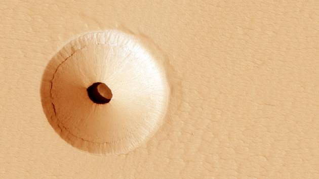 """Tajuplná """"díra"""" na povrchu Marsu byla objevena náhodou v roce 2011 při snímkování sopečného štítu Pavonis Mons kamerou HiRISE, umístěnou na palubě americké planetární sondy Mars Reconnaissance Orbiter, kroužící kolem Marsu"""