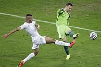 Brankář Ruska Igor Akinfejev (vpravo) vykopává míč před dotírajícím Islámem Slimaním z Alžírska.