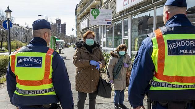 Maďarští policisté na ulici ve městě Békéscsaba kontrolují dodržování nařízení vydaných v souvislosti s koronavirovou epidemií