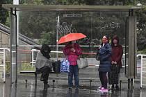 Lidé se kryjí na zastávce před deštěm 11. května 2020 v Praze