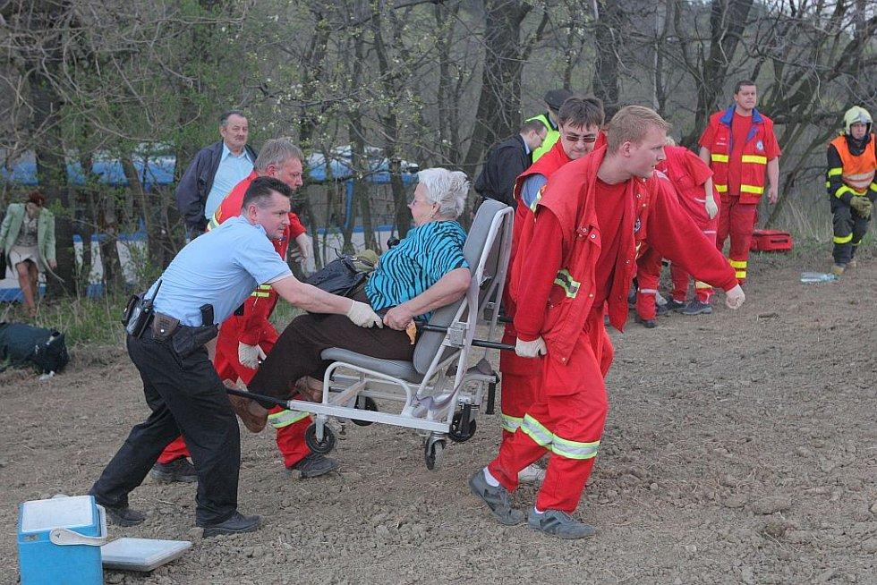 Záchranáři dopravují zraněné cestující k ošetření