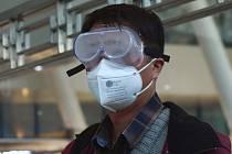 Muž v zamlžených brýlích a respirátorové masce čeká 15. dubna 2020 na nádraží v čínském Wu-chanu na vlak do Pekingu