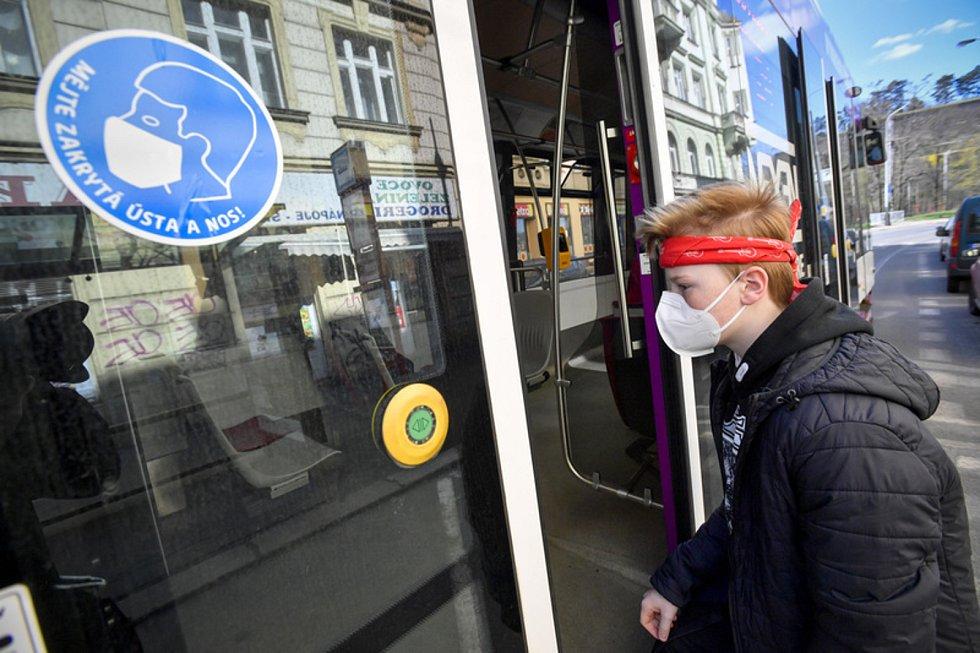 Chlapec s rouškou v pražské tramvaji