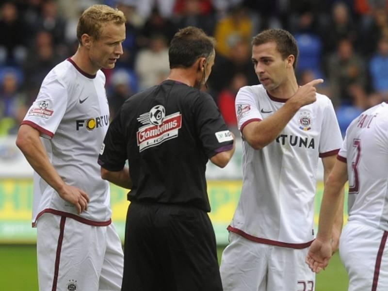 Fotbalisté Sparty Jiří Jarošík (vlevo) a Josef Hušbauer (vpravo) diskutují s rozhodčím Radkem Matějkou.
