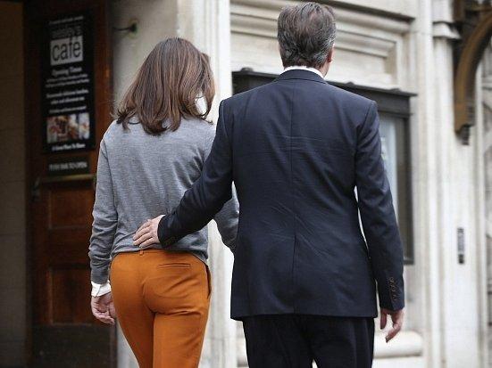 Britský premiér David Cameron s manželkou Samanthou opouštějí volební místnost