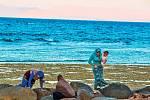 Místní ženy při odlivu hledají na pobřeží chobotnice a další živočichy k jídlu.