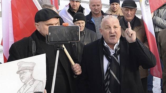 Krajně pravicoví aktivisté před památníkem v Osvětimi. V popředí lídr Piotr Rybak