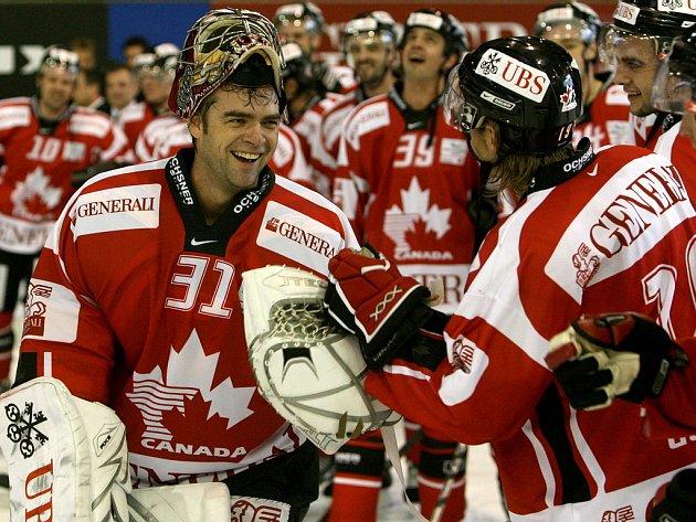 Kanadský brankář Curtis Joseph (vlevo) přijímá gratulace od spoluhráčů po vítězství svého týmu ve finále Spengler Cupu. Kanaďané zdolali Ufu 2:1.