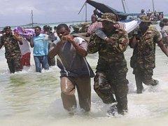 Záchranáři vynášejí oběti převrácení trajektu na Viktoriině jezeře.