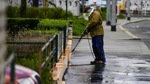 Muž dezinfikuje jako prevenci proti nákaze novým typem koronaviru 14. dubna 2020 prostranství před domem ve Strašnicích v Praze.
