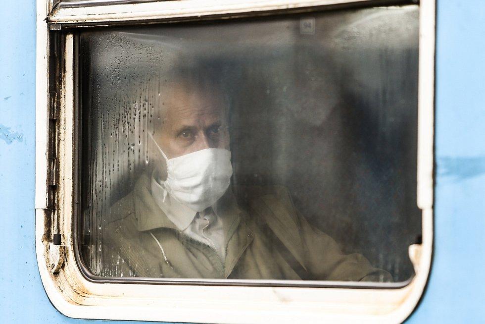 Senior s rouškou ve vlaku na kolínském nádraží.