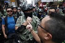 Demonstrant hovoří s policistou při protestech v Hongkongu