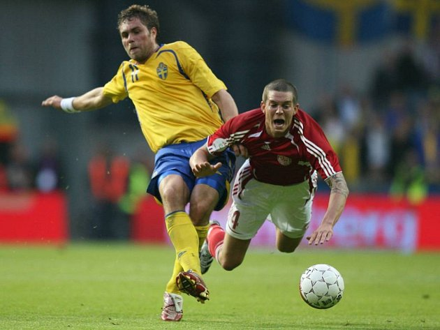 Dán Daniel Agger (v červeném) v souboji se Švédem Johanem Elmanderem. Snažení hráčů nakonec zmařil rozhořčený fanoušek.