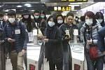 Lidé míří v ochranných maskách 28. ledna 2020 do metra v Tchaj-peji.