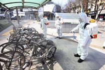 Jihokorejští vojáci v ochranných oděvech dezinfikují cyklostojan s koly na ulici v Tegu.