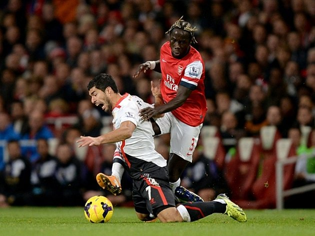 Luis Suarez z Liverpoolu (vlevo) se poroučí k zemi po faulu Bacary Sagny z Arsenalu.