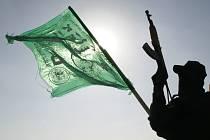 Bojovník Hamásu stojí na stráži vedle vlajky svého hnutí na střeše jedné z obsazených úřadoven konkurenčního Fatáhu.