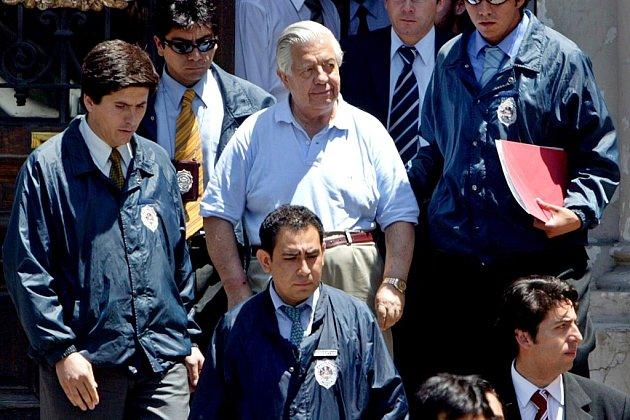 Policisté odvádějí k výslechu někdejšího šéfa obávané chilské tajné policie DINA Manuela Contrerase, vyšetřovaného kvůli zločinům, kterých se on a jeho muži v 70. letech s posvěcením Augusta Pinocheta dopouštěli. (Snímek je z května 2005.)