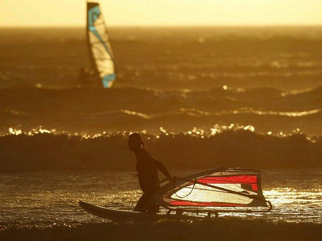 Surfaři a kitesurfaři si užívají příhodné počasí na jihoafrickém pobřeží v zátoce Big Bay v Kapském Městě na Boží hod vánoční.