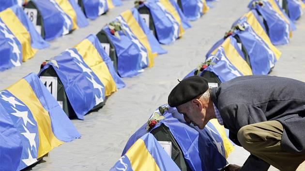 Bosenský Muslim líbá kazety s ostatky obětí války, pokraté vlajkami Bosny a Hercegoviny a připravené k slavnostnímu pohřbení.