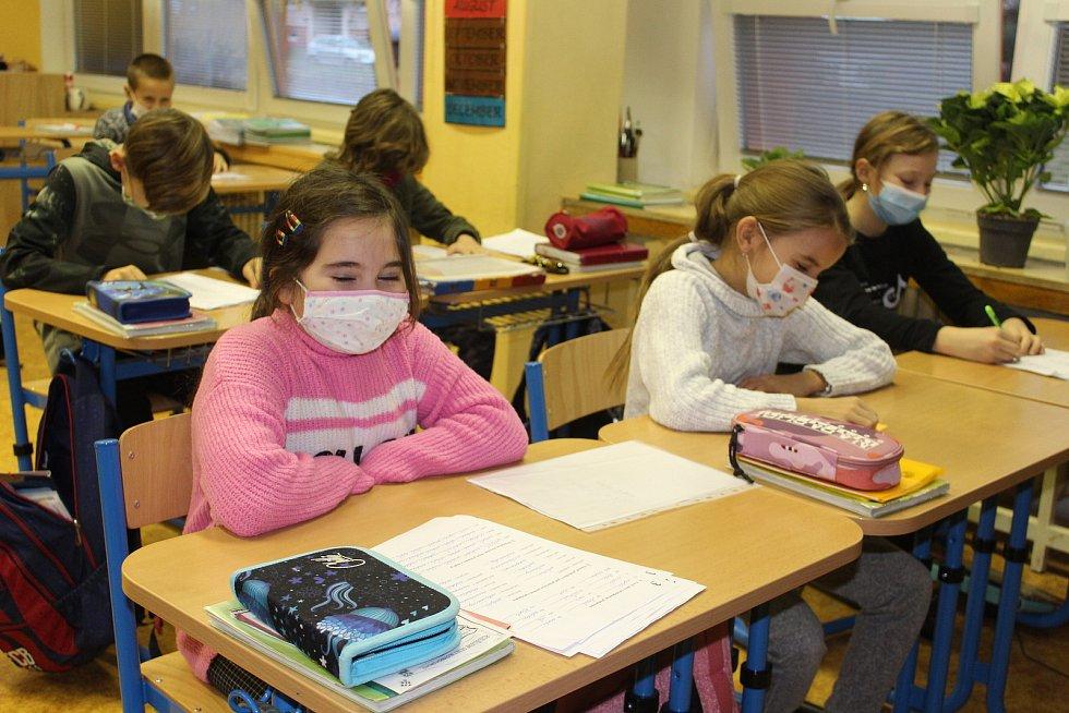 Výuka na první stupni v době koronaviru? Žáci sedí v rouškách a na třetí ze čtyř vyučovacích hodin se celá třída chodí ven provětrat.
