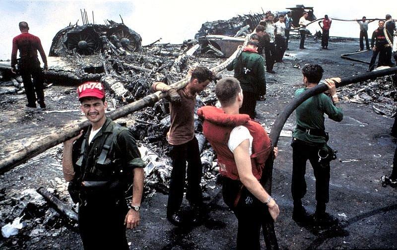 Zbylí vyčerpaní členové posádky Forrestalu stojí nad ohořelými troskami po palubním požáru, který si vyžádal životy 134 jejich druhů