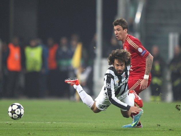 Andrea Pirlo z Juventusu Turín (vlevo) plachtí po kontaktu s Mariem Mandzukičem z Bayernu Mnichov.