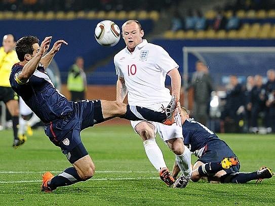 Wayne Rooney se dere obranou USA.