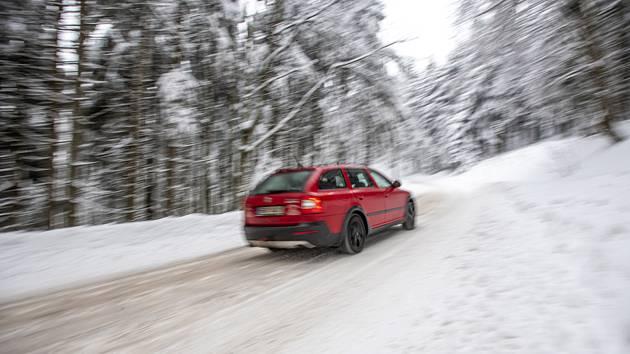 Automobil projíždí po zasněžené silnici. Ilustrační snímek