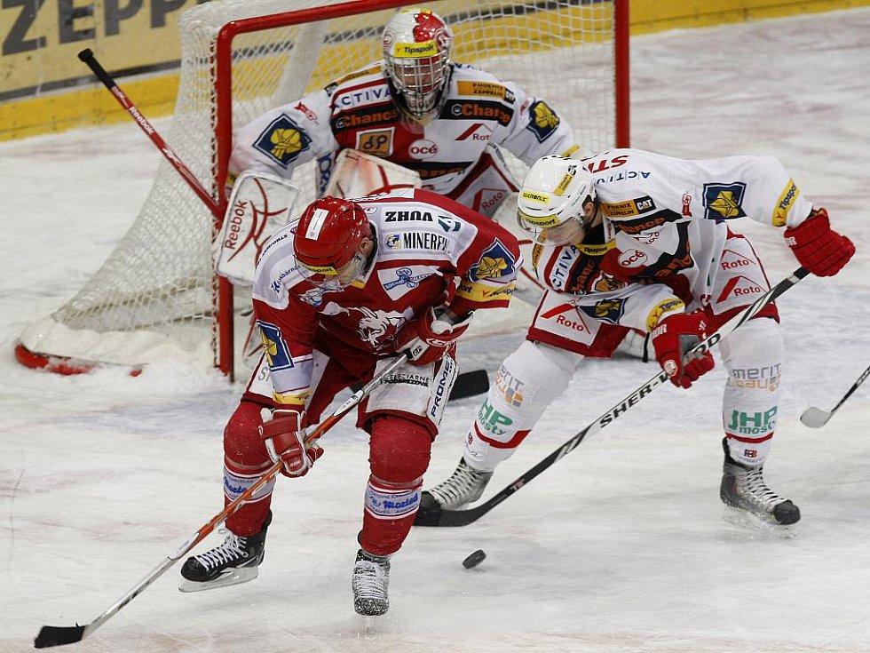 Petr Kadlec (v bílém) ze Slavie bojuje o puk s Martinem Růžičkou z Třince před gólmanem Miroslavem Kopřivou.