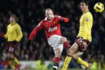 Hvězda Manchesteru United Wayne Rooney (uprostřed) pálí před Marouane Chamakha z Arsenalu.