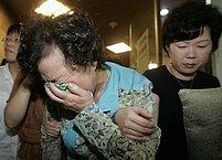 Matka a rodina uneseného devětadvacetiletého Šim Sung-mina pláče poté, co viděli televizní zpravodajství....