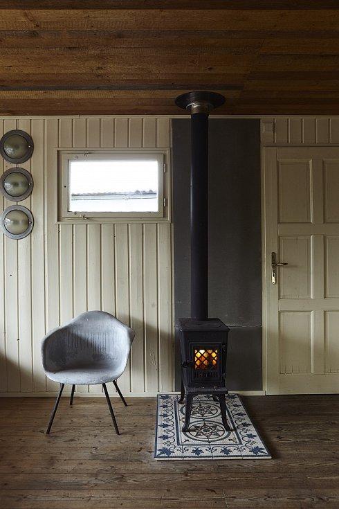 Kamínka Jotul z minulého století vypadala v dřevěné chatě jako šperk, proto se Martina a Hynek rozhodli posílit tento dojem ještě dlažbou s dekorem ze stejné doby.