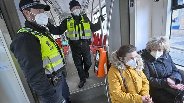 Příslušníci městské policie dohlížejí 25. února 2021 v tramvaji pražské MHD na dodržování nově zavedené povinnosti nosit na frekventovaných místech respirátor