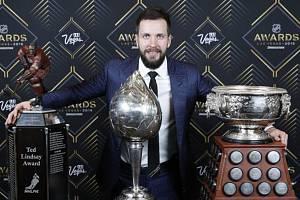 Hokejový útočník Nikita Kučerov z Tampy Bay s trofejemi na vyhlášení cen NHL v Las Vegas, zleva Ted Lindsay Award, Hart Memorial Trophy a Art Ross Trophy.
