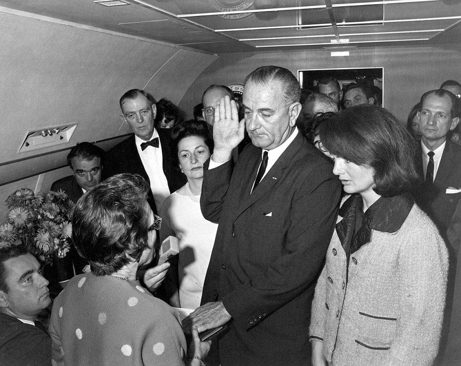 V AIR FORCE ONE.  L. B. Johnson přísahá 22. 11. 1963 při letu z Dallasu nad  rakví zavražděného J. F. Kennedyho.