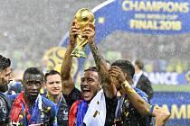 Fotbalista Francie Corentin Tolisso se raduje s trofejí pro mistry světa.