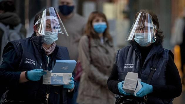 Zaměstnankyně německých drah rozdávají roušky cestujícím na vlakovém nádraží ve Frankfurtu nad Mohanem