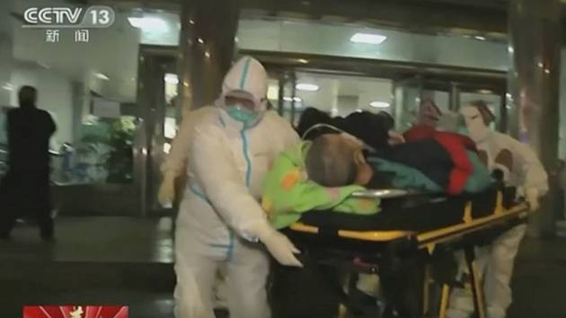 Zdravotníci v ochranných oblecích transportují pacienta do nemocnice ve městě Wu-chan