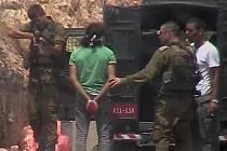 Izraelský voják střílí na spoutaného Palestince, zadrženého ve vesnici Nilin.