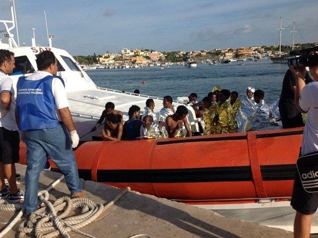 Italská pobřežní stráž se zachráněnými imigranty z potopené lodi u ostrova Lampedusa.