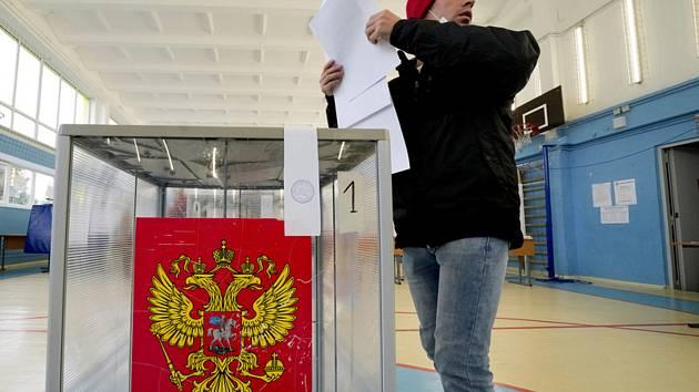 Muž odevzdává svůj hlas v Petrohradě 17. září 2021 během parlamentních voleb v Rusku